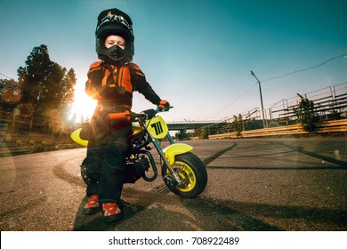Child on his small motorcycle. Small biker dressed in a protective suit and helmet.