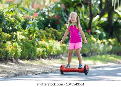 Child on hover board. Kids riding scooter in summer park. Balance board for children. Electric self balancing scooter on city street. Girl learning to ride hoverboard. Modern gadgets for school kid