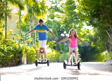 Child on hover board. Kids riding scooter in summer park. Balance board for children. Electric self balancing scooter. Girl and boy learning to ride hoverboard. Modern gadgets for school kid.
