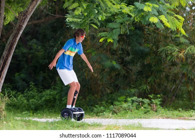 Child on hover board. Kids riding scooter in summer park. Balance board for children. Electric self balancing scooter on city street. Boy learning to ride hoverboard. Modern gadgets for school kid.