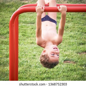 Child on monkey bars. Kid at beach playground. Little boy hanging on gym activity center of preschool play ground. Healthy outdoor activity for kids. Sport for young children.