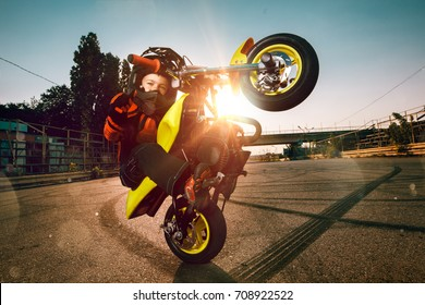 Child on a motorcycle doing moto stunt. Small boy get a difficult and dangerous trick on his small morocycle. Small biker dressed in a protective suit and helmet.