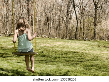 Child on an old-fashioned tree swing