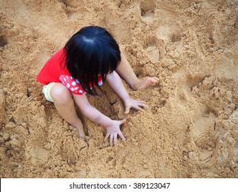 Child on playground sand in summer park