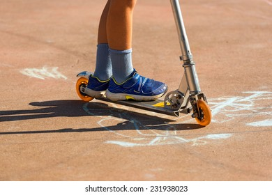 Child on a Scooter / Feet of a child with sneakers on a metal scooter. Pavement with drawings made with chalk