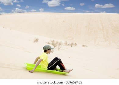 Child on a sled pulls off the sandy mountains.  Monahans Sandhills State Park, Texas, USA