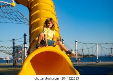 Child on slide playground area. Funny cute kid sit on tunnel slide on playground.