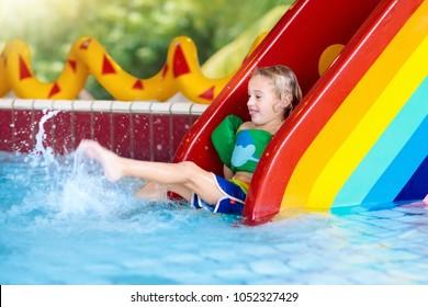 e4113b2c8a7d9 Child on swimming pool slide. Kid having fun sliding in water amusement  park. Kids