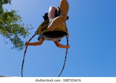 Child on a swing, viewed from below, blue sky background