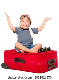Child on Travel Suitcase, Kid in Pilot Hat Sitting on Red Luggage, Happy Boy Open Arms Isolated over White Background