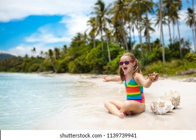 Child on tropical beach. Kid with sea shell relaxing at ocean shore during family summer vacation. Little girl playing with seashells on exotic island in Asia. Travel with kids. Children at ocean.
