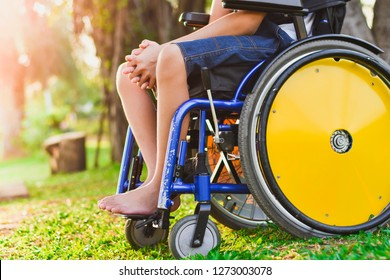 Child on the wheelchair in the park. Close-Up his wheel.