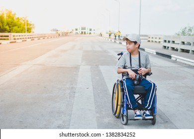 A child on wheelchair is smile happily, Amateur photographer hold camera in hand, Bridge  background and day light, Life in the education age of disabled children, Happy disabled kid concept.