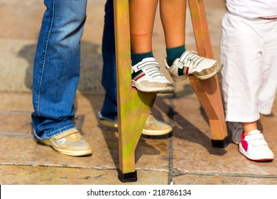 Child on Wooden Stilts / An adult helps a child to walk on wooden stilts, view of sun legs and feet