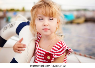 child on a yacht in red and white striped T-shirt in summer