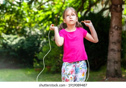 Child, one little girl jumping using a skipping rope alone, outdoors lifestyle shot. Kid using a jump rope outside. School age children and physical activity, having fun, exercising simple concept