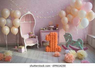 The child is one year old. room decorated with balloons with a gift cake, a toy horse and a large number one of colored paper.