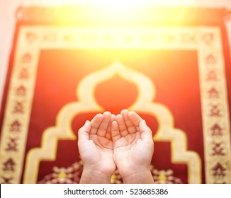 Child open empty hands with palms up. On the floor a prayer rug