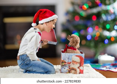 a child opening a christmas gift box with a puppy inside