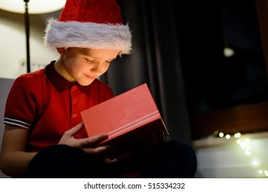 Child opening gift box from Santa Claus. Wears red Santa Claus hat and red polo shirt