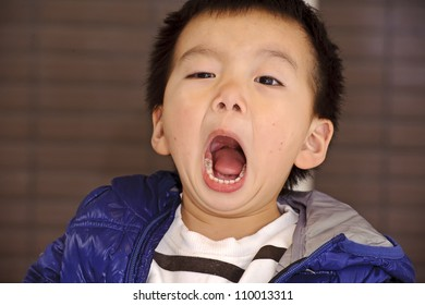 A child opening his mouth and shouting