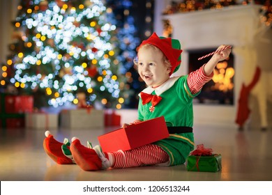 19613310d Child opening present at Christmas tree at home. Kid in elf costume with  Xmas gifts