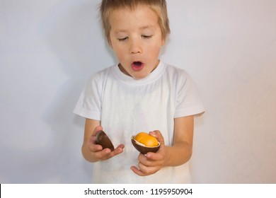 A child opens a chocolate egg. The boy is surprised by the surprise.