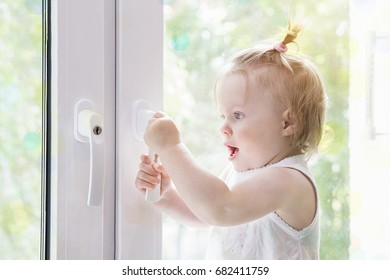 Child opens window with  lock close up. Child at window macro. Window with lock for children's safety.