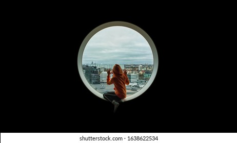 Child with orange hood jacket sit and longing out looking through round glass window from above over a city.