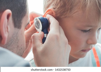 A child with otitis at the reception at the children's otolaryngologist in the hospital. Cute boy with bad ears at the doctor's office in the clinic.