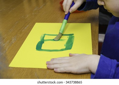 Child paint art with green paint and paint brush
