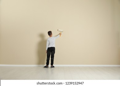 Child painting color wall with roller brush. Space for text