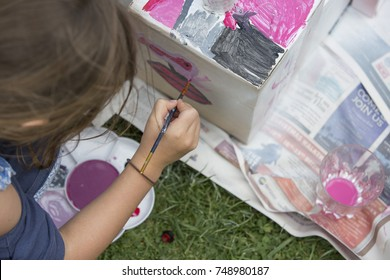 Child painting with colored paints on a cardboard box outside on the grass