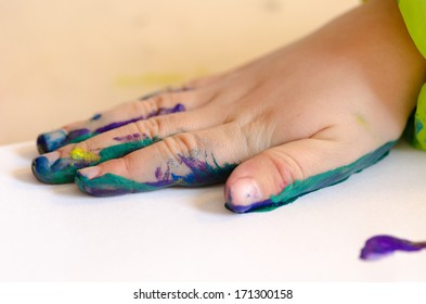 Child painting its hands in order to make a print on paper