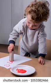 Child painting hearts with a wC paper carton