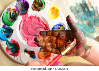 Child painting her hand with a paintbrush and background with palette of colorful paint
