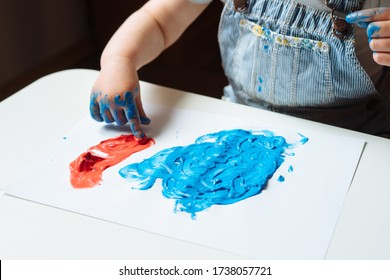 Child painting with her hands on the table at home using blue and red paint. Finger painting or art therapy for children. Fun activities for toddlers. Close up.