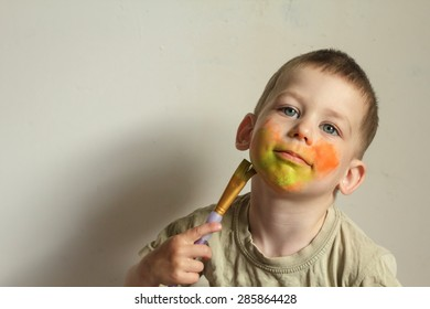 Child painting his face with aqua-color body painting with a brush