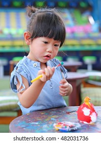 Child painting, little girl having fun to paint on stucco doll