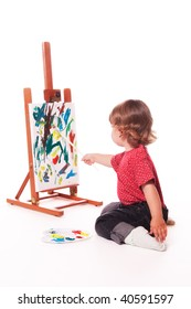 Child painting on easel with paintbrush