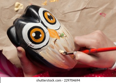 Child painting an owl made of recycled plastic bottle.