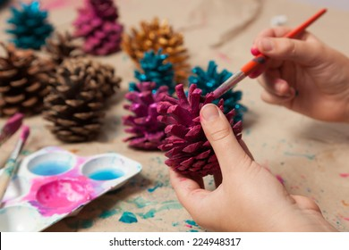 Child painting pine cones as homemade Christmas ornaments.