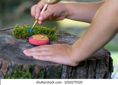 A child painting a rock placed on a tree stump