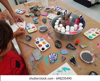 child painting rocks on a table with colored paints