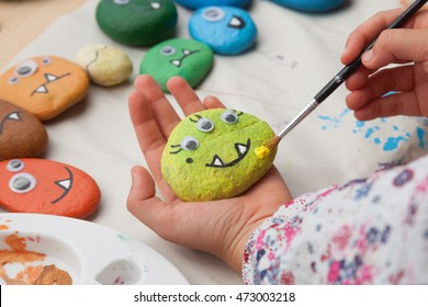 Child painting a stone monster craft