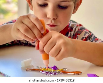 A child painting suncatcher with color paints. Toddler crafts. Arts and crafts for kids. Selective focus
