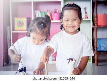 Child painting, two little girl having fun to paint on stucco doll together on bookshelf background,selective focus
