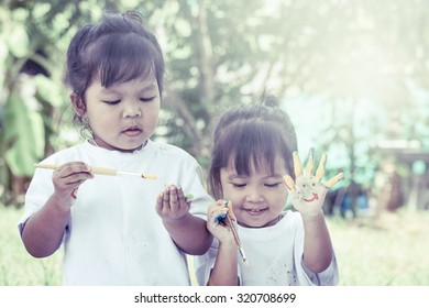 Child painting, two little girl having fun to paint on hands together in garden in vintage filter,selective focus