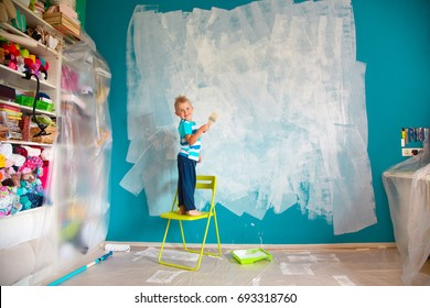 The child paints the blue wall with a roller. The boy holds a large brush for painting. Home repairs.