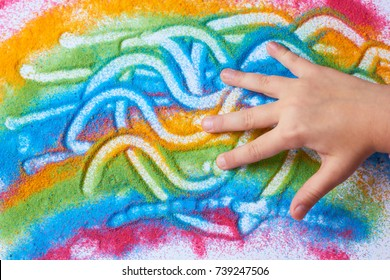 The child paints with colored sand on a white sheet